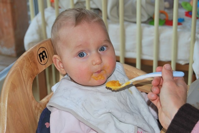 a baby is eating baby food