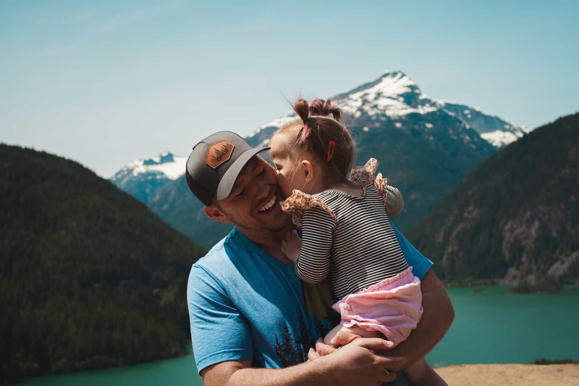 child kisses dad in front of mountain and lake