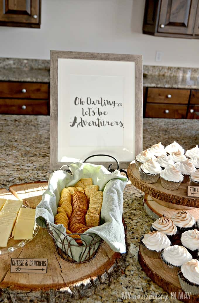 platter of cheese with an assortment of crackers and mores cup cakes