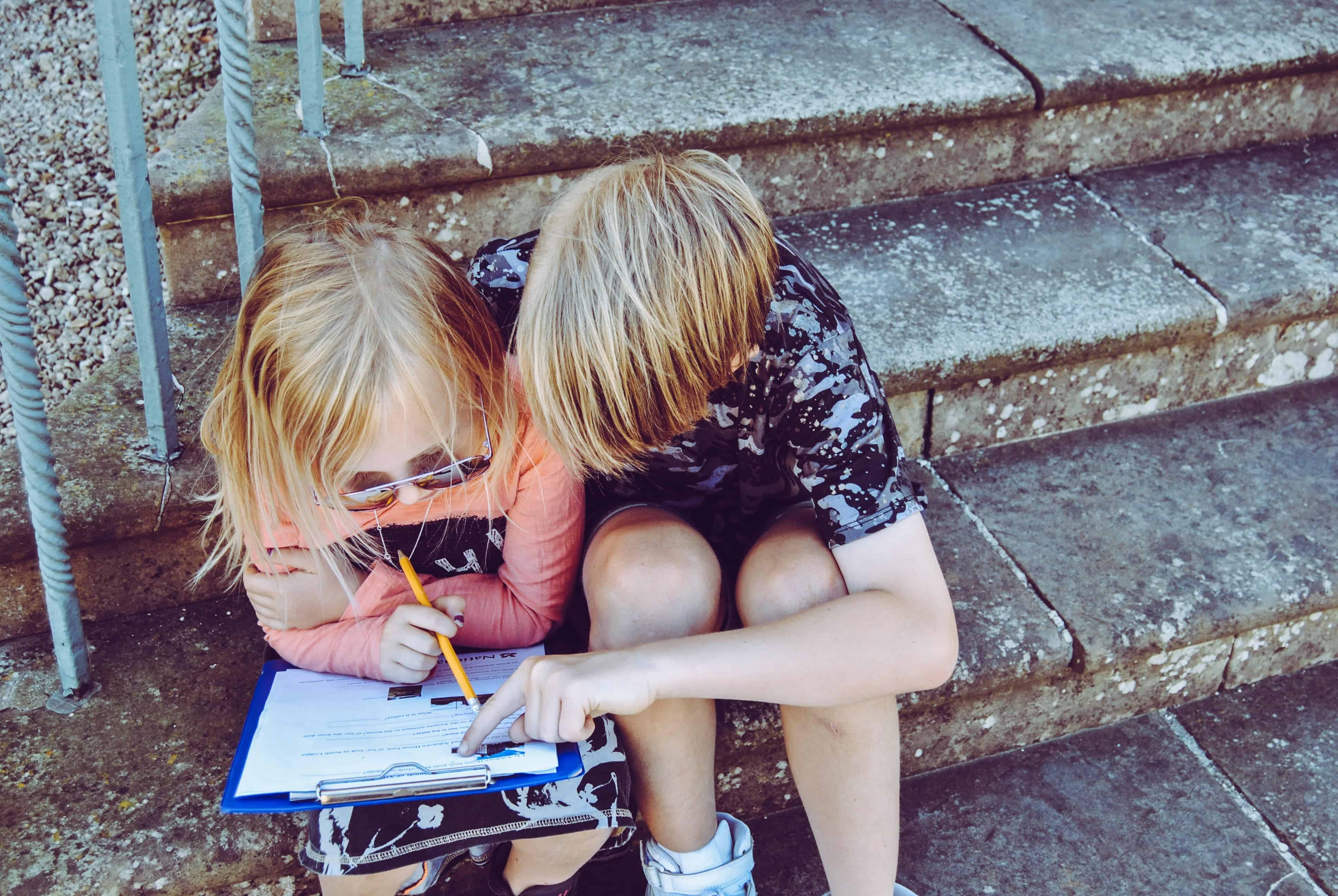 kids on stairs with a book
