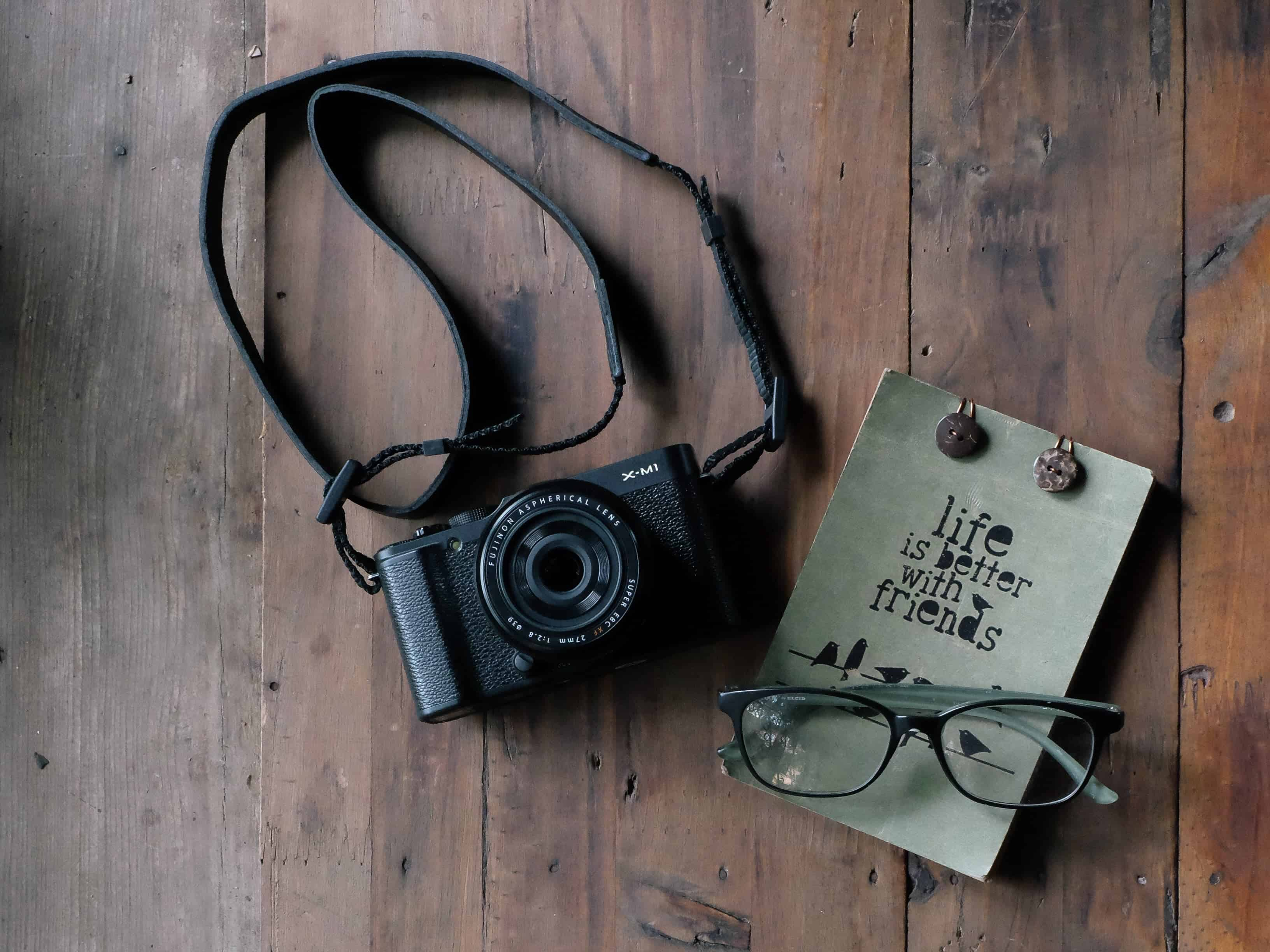 black camera with book on wooden table
