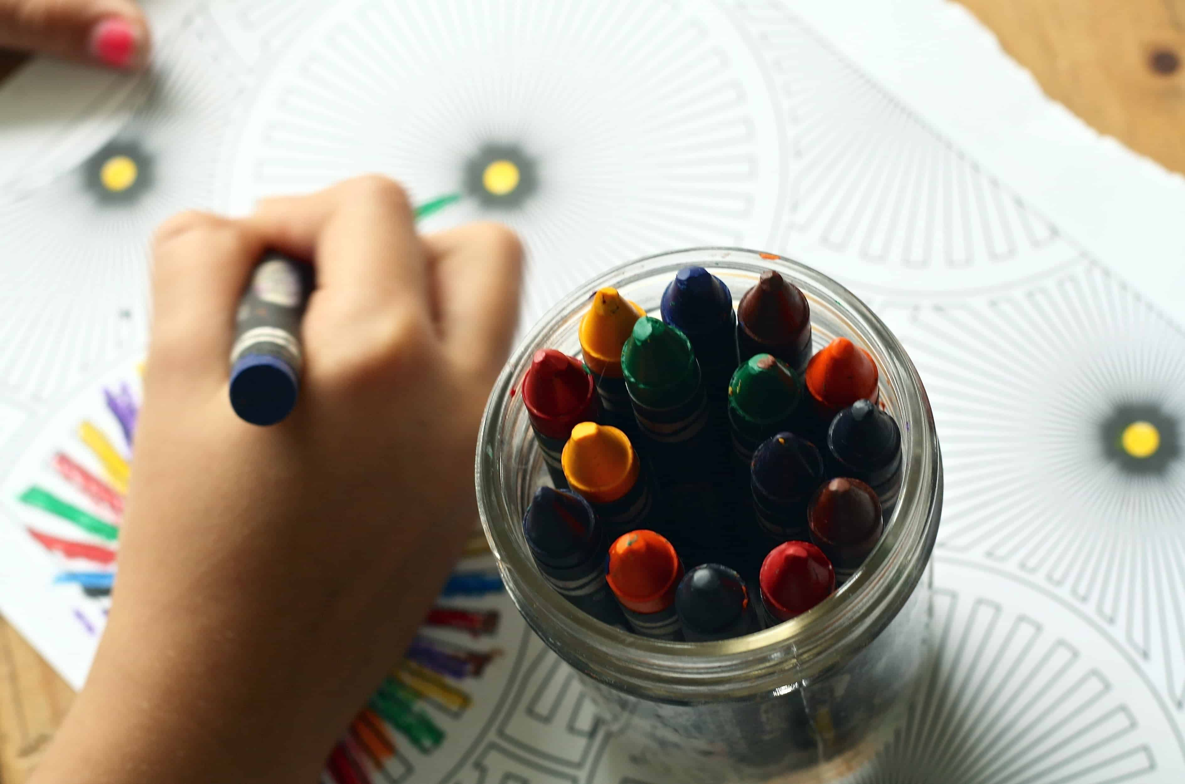boy coloring with crayons on paper