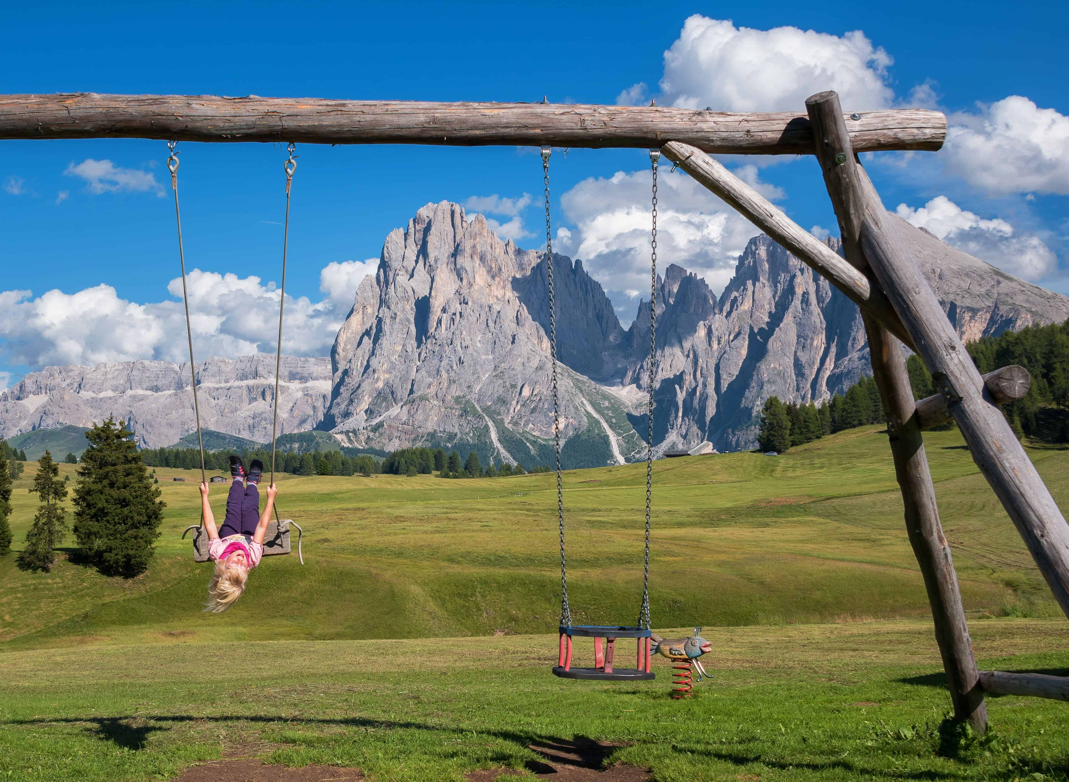 child swinging on a swings in the mountains
