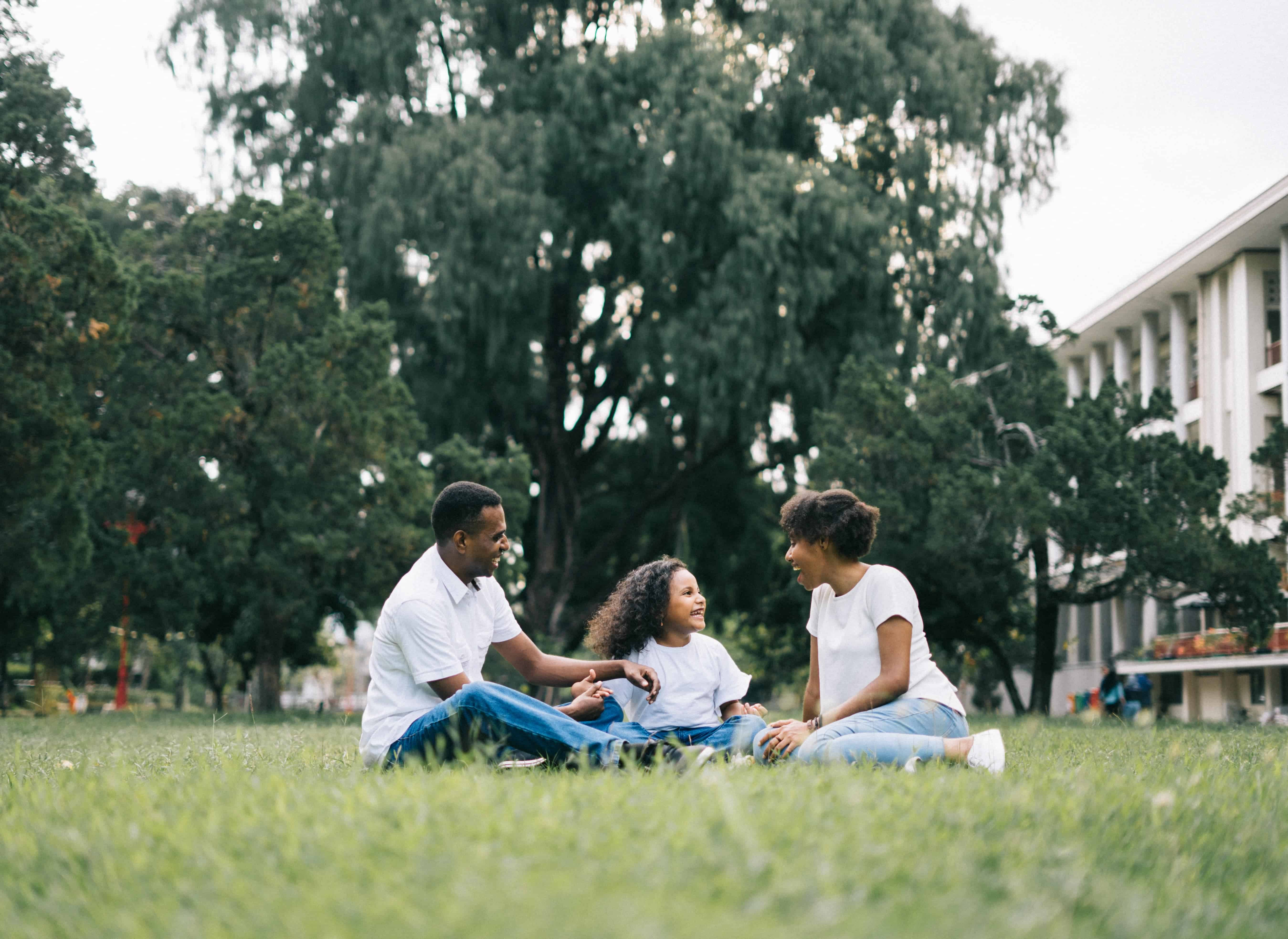 african american parents and child sitting on lawn