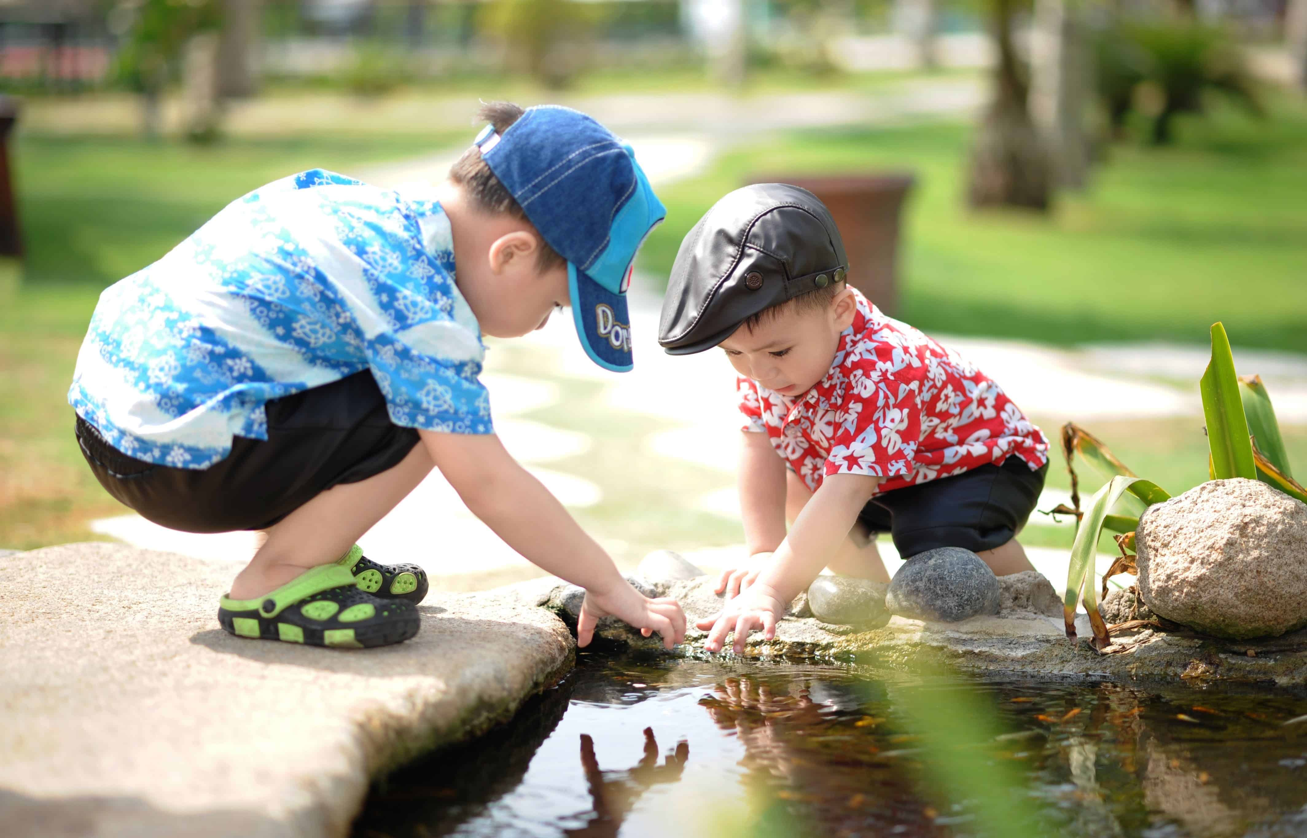 two boys playing in a stream