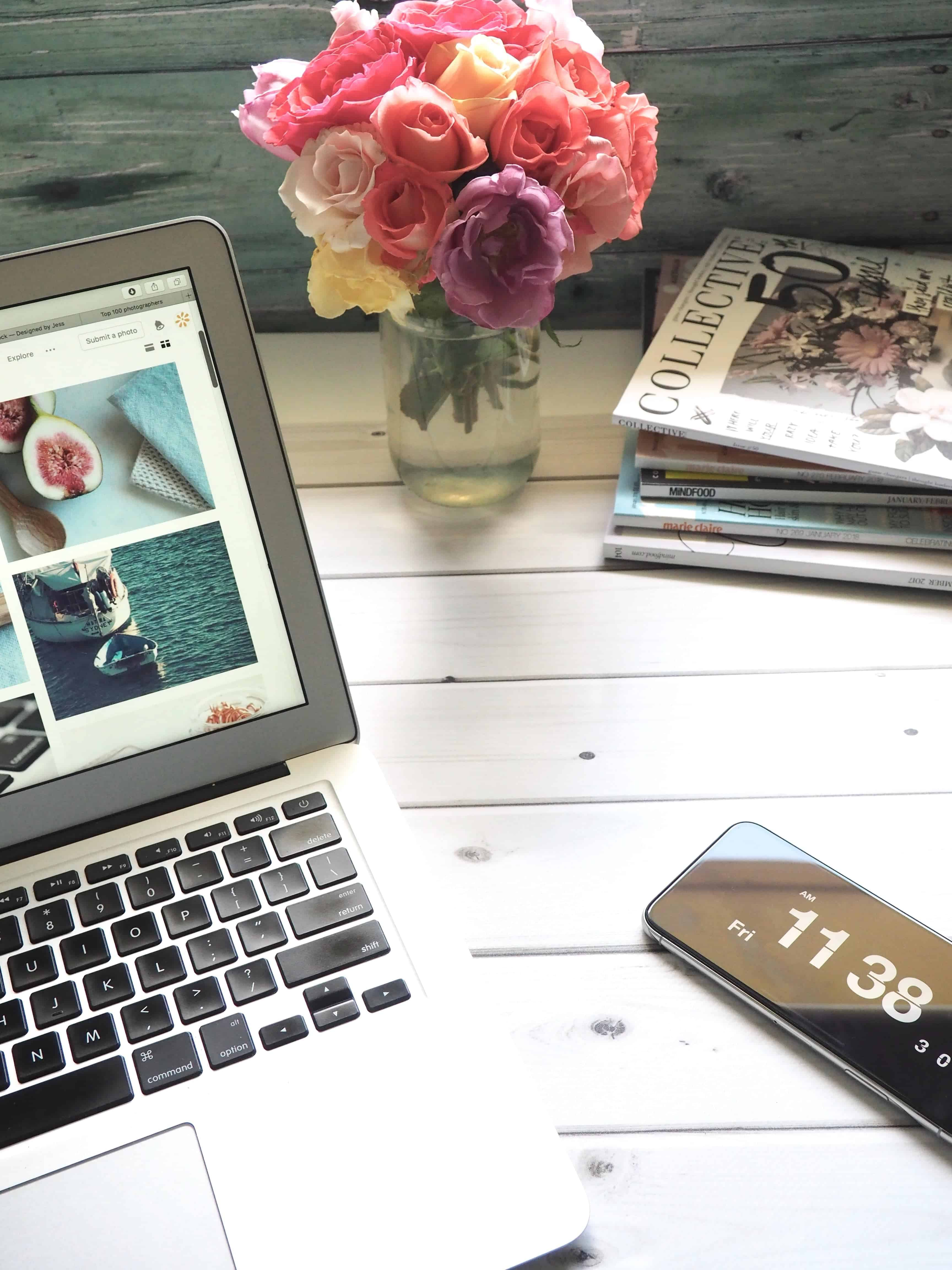 flat lay of laptop, phone and magazines