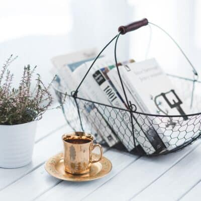 basket with books, golden mug and lavender